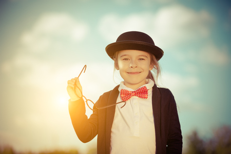 Funny little girl in bow tie and bowler hat holding glasses. Retro stile. Stock Photo