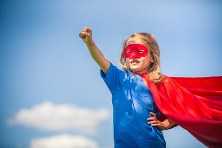super man: Funny little girl playing power super hero over blue sky background. Superhero concept. Stock Photo