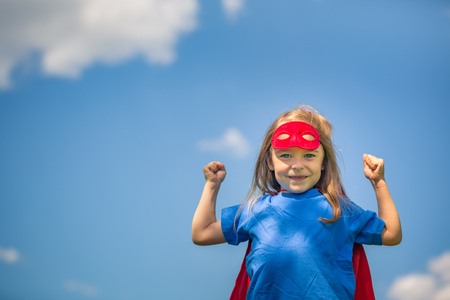 pretend: Funny little girl playing power super hero over blue sky background. Superhero concept. Stock Photo