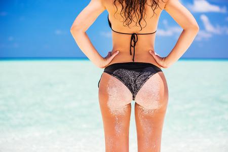 Back of young woman in bikini standing on the ocean beach Stock Photo