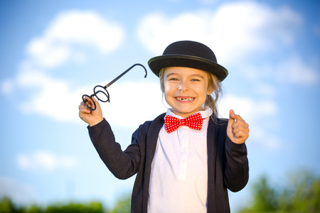 Funny little girl in bow tie and bowler hat holding glasses. Retro stile. Banque d'images
