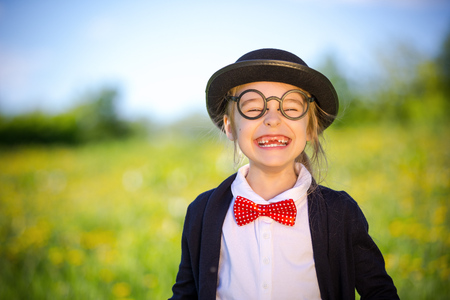 Funny happy little girl in bow tie and bowler hat. Retro stile.