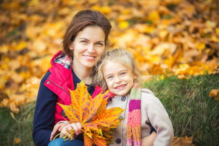 Smiling little girl and her mother enjoy walk in autumn park and play with bright autumn leaves Stock Photo
