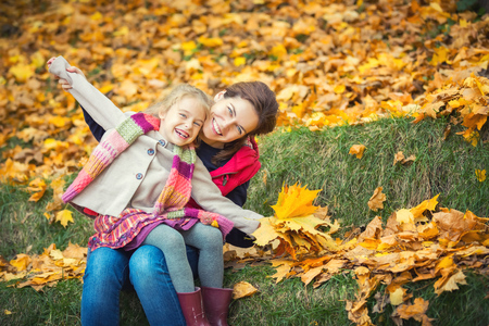 Happy little girl and her mother enjoy walk in autumn park and play with bright autumn leaves Stock Photo