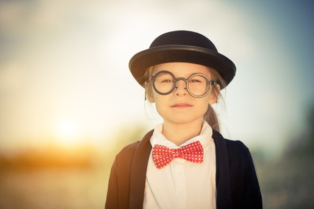 Outdoor portrait of funny little girl in bow tie and bowler hat. Retro stile. Stock Photo