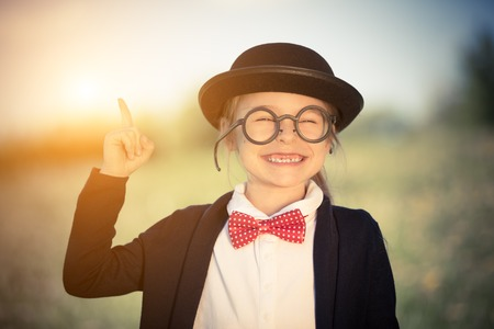 Outdoor portrait of funny little girl in glasses, bow tie and bowler hat pointing finger up. Retro stile.