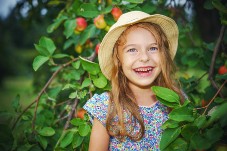 Happy little girl in apple garden
