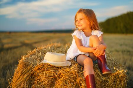 Little girl in a field with hay rolls at sunset Banque d'images