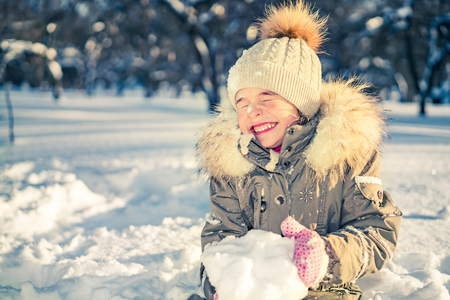 Little girl playing with snow in sunny winter park Stock Photo
