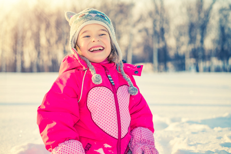 Little girl playing with snow at sunny and frozen winter day Banque d'images