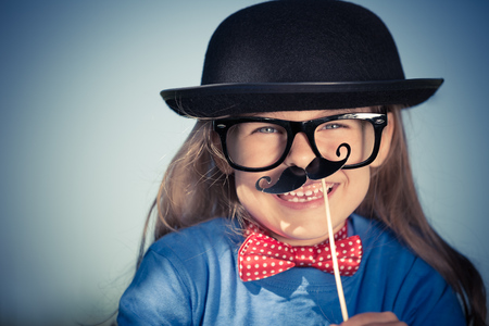 Outdoor portrait of funny happy little girl in bow tie and bowler hat. Retro stile. Stock Photo