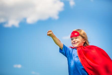 Funny little girl playing power super hero over blue sky background. Superhero concept. 版權商用圖片