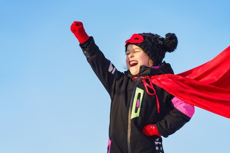 Funny little girl playing power super hero over blue sky background. Superhero concept. Imagens