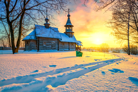 Small russian church in winter park at sunset