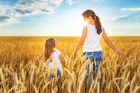 Young woman and her daughter walking on golden wheat field at sunny summer day.
