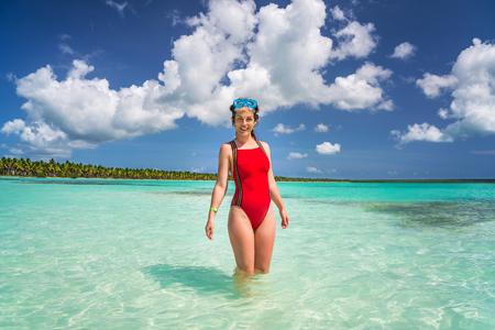 Young woman in bikini and scuba mask standing on the beach in Dominican Republic 免版税图像