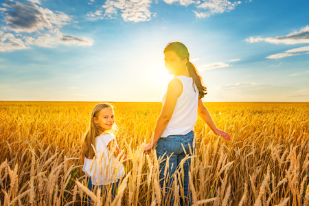 Young woman and her daughter walking on golden wheat field at sunny summer evening.