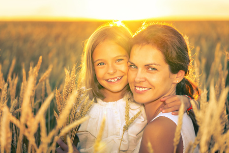 Young woman and her daughter on golden wheat field at sunny summer evening. Imagens