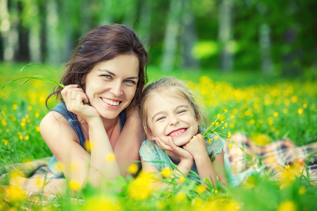 Mother and daughter lying on green summer meadow with blooming yellow flowers