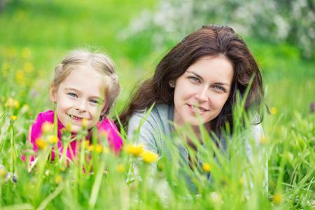 Madre e hija tumbada en la hierba verde del verano con flores amarillas florecientes