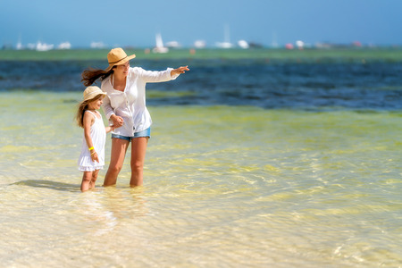 Young mother and little daughter standing on the beach in Dominican Republic
