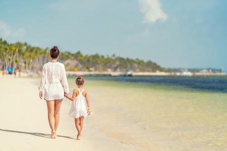 Young mother and little daughter walking on the beach in Dominican Republic