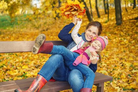 Happy little girl and her mother have fun sitting on the bench in autumn park