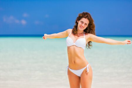 Happy young woman in bikini enjoing the beautiful ocean beach on Maldives