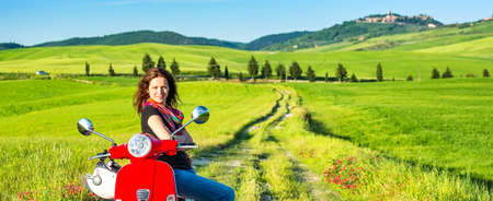 Portrait of young beautiful woman with a scooter and tuscany landscape in background 免版税图像