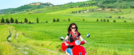 Young beautiful woman traveling by a scooter in tuscany