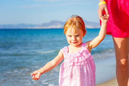 Little girl holding mothers hand walk on the sea beach in Greece