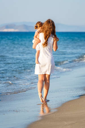 Mother with little daughter walking on the sea beach in Greece