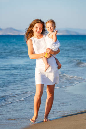 Portrait of mother and little daughter on the sea beach in Greece 免版税图像