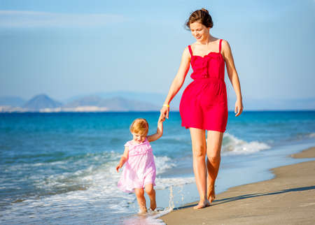 Mother and little daughter walking on the sea beach in Greece 免版税图像
