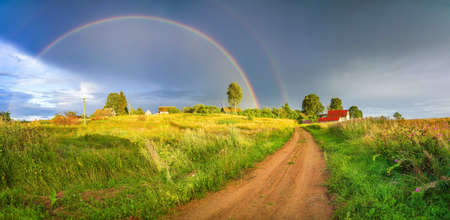 Rainbow over stormy sky. Rural landscape with rainbow over dark stormy sky in a countryside at summer evening.