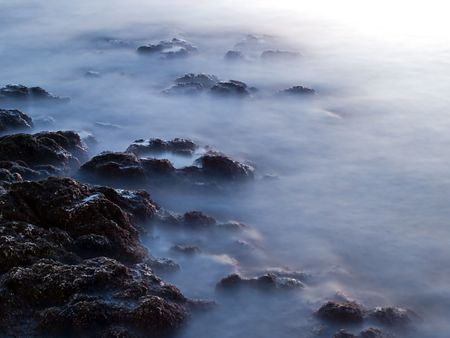 dimly: Rock surrounded by wayes and water-foam  like sea spray. Motion blur