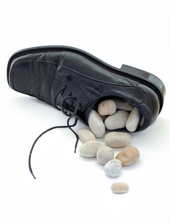 figurative: Metaphor about problems like  small stone at the bottom of shoe.What to do when it is full, and they are no longer small Stock Photo