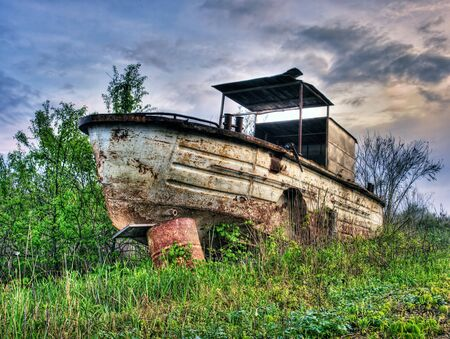 Old,rusty and abandoned river boat  in HDR technique Stock Photo