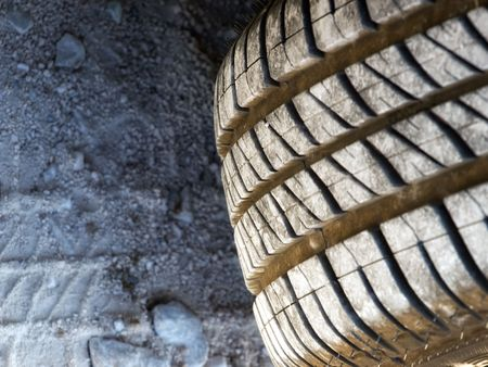 Closer look at the texture of summer tires, which is more expressed at the dirty road. Stock Photo