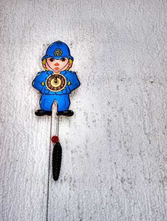 englishman: Clock with the figure of policeman on the old grungy wall may represent police hour.