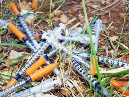 Used syringes discarded somewhere in  nature  pose a risk of infection Stock Photo - 5452163