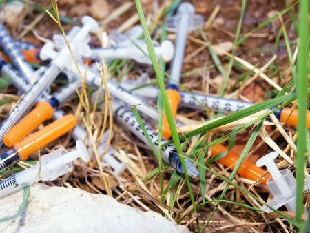 Used syringes discarded somewhere in  nature  pose a risk of infection Stock Photo - 5486743