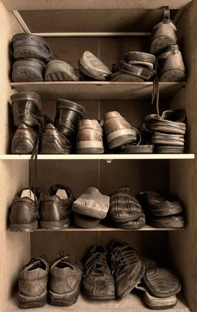 Toned image of an old wooden shoes box with a lot of different footwear inside. photo