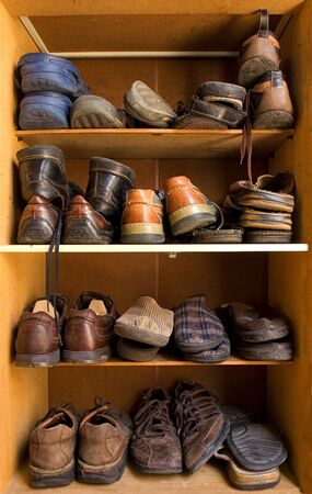 shoe shelf:  An old wooden shoes box with a lot of different footwear inside.