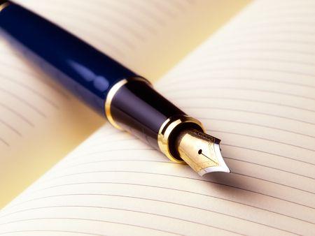 lapiceros: Pluma estilogr�fica en una p�gina en blanco abierta en un libro de diario...