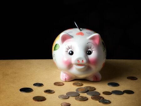Coin bank like piggy and coins in front of it... Stock Photo - 5683651