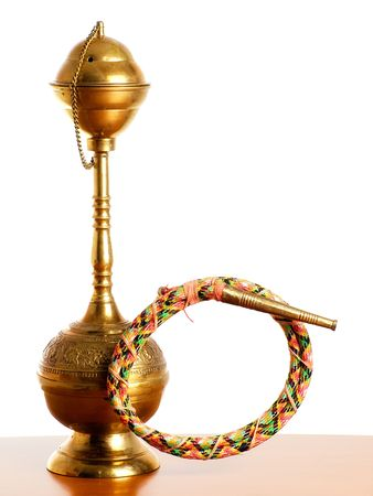 Golden metal narghile or hookah on a bright background. Stock Photo - 5815248