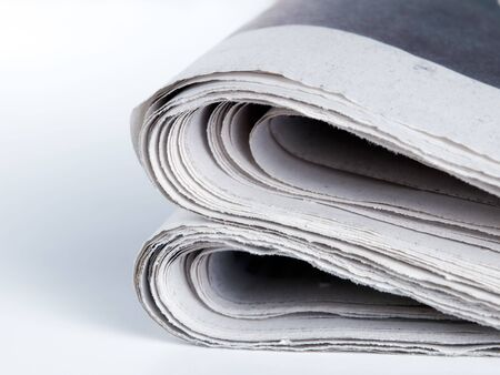 broadsheet: Folded edges of the  newspaper on a clear background.