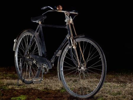 Old-fashioned black bicycle on a dark background. photo