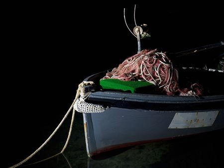 Fishing boat with heap of  nets on it, somewhere in the darkness. photo